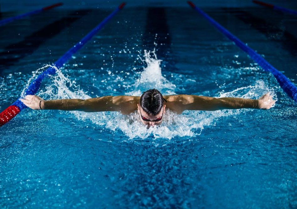 Swimmer swimming with custom earplugs for swimming